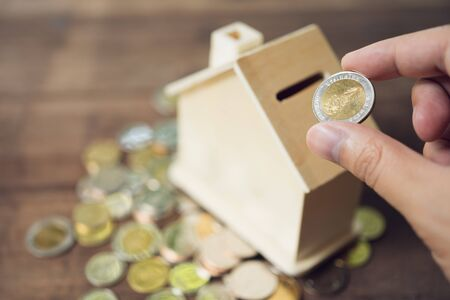 Business men Put the coin in House style piggy bank To save money, save money on investments, spend money when needed And use in the future. Investment concept. Savings with copy spaces.