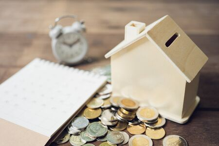 A model house model is placed on a pile of coins.using as background business concept and real estate concept with copy space for your text or design. 写真素材 - 130117516