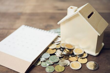 A model house model is placed on a pile of coins.using as background business concept and real estate concept with copy space for your text or design. 写真素材 - 130117787