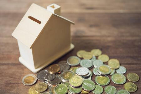 A model house model is placed on a pile of coins.using as background business concept and real estate concept with copy space for your text or design.