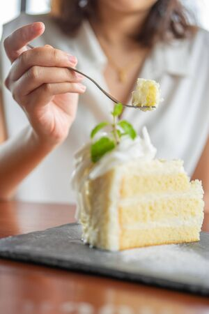 Asian beauty Scooping the cake to eat In Caffe Holiday idea Eating sweets, the cause of obesity, weight gain, poor health Stock Photo
