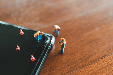 Miniature people Construction worker  repair smartphone using as background Maintenance concept and repair concept with copy space for your text or design.