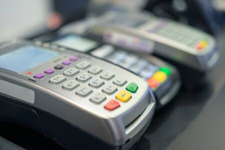 Credit card swipe machine And a young woman holding a credit card to pay for purchases using money from the card. Or installment payments Фото со стока
