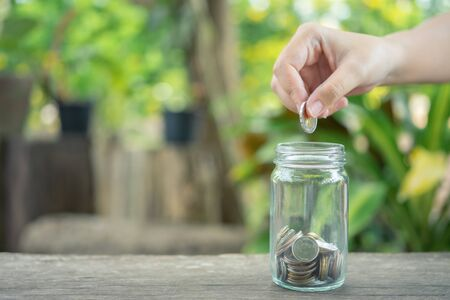 Businessmen Put the coin in a glass jar To save money, save money on investments, spend money when needed And use in the future. Investment concept. Savings with copy spaces.