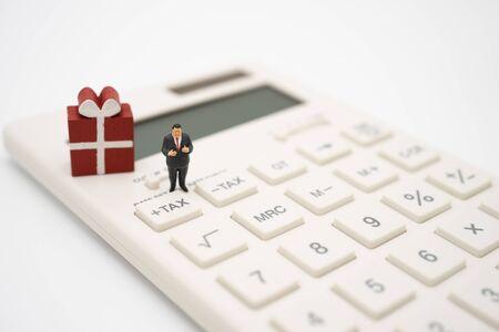 Persone in miniatura Paga in coda Reddito annuale (TAX) per l'anno sulla calcolatrice. utilizzando come sfondo il concetto di business e il concetto di finanza con copia spazio per il tuo testo o design.
