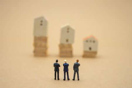Miniature 3 people businessmen standing with back Negotiating in business. as background business concept and strategy concept with copy space.