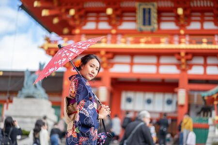 Geishas girl wearing Japanese kimono among red wooden Tori Gate at Fushimi Inari Shrine in Kyoto, Kimono is a Japanese traditional garment. The word kimono, which actually means a thing to wear