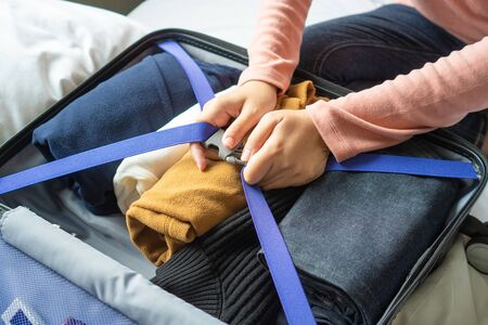 Happy young woman hands packing clothes into travel luggage on bed at home or hotel room for a new journey.  Tourism and vacation concept Banque d'images - 135499220