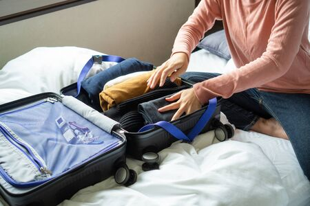 Happy young woman hands packing clothes into travel luggage on bed at home or hotel room for a new journey.  Tourism and vacation concept Banque d'images - 135499224