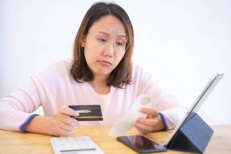 Confused portrait young woman holding credit cards having problem online payment with credit card making rejected unsecure online payment. credit card debt payment Foto de archivo - 135499474