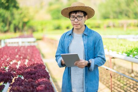 Portrait of young smart farmer using digital tablet computer for inspecting. using technology in agriculture field application in agricultural growing activity and checking quality concept.