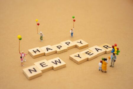 Family Miniature people standing with wood word Happy new year using as background Universal day concept and Happy new year concept with copy space  for your text or design. Zdjęcie Seryjne