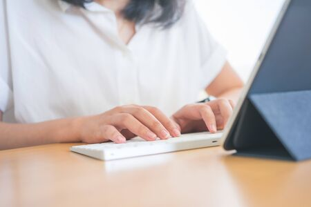 Young Freelancer or Businessman working at home office and typing on keyboard smartphone tablet. Working Online Or Studying And Learning While Using smartphone tablet. Freelance Work, Business concept Zdjęcie Seryjne
