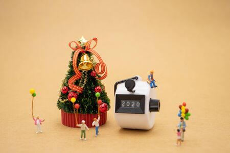 Happy Family Miniature people standing on Christmas tree Celebrate Christmas on December 25 every year. using as background xmas concept with copy spaces for you