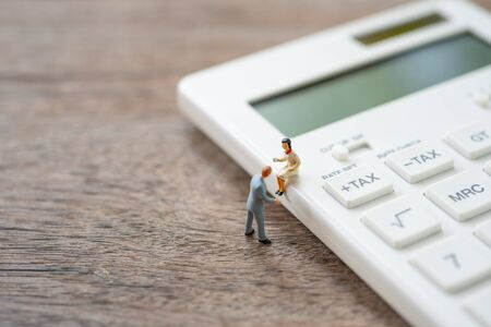 Miniature people sitting on white calculator using as background business concept and teamwork concept with copy space and white space.