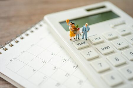 Family Miniature people Pay queue Annual income (TAX) for the year on calculator. using as background business concept and finance concept with copy space  for your text or design.