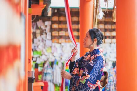 Geishas girl wearing Japanese kimono among red wooden Tori Gate at Fushimi Inari Shrine in Kyoto, Kimono is a Japanese traditional garment. The word