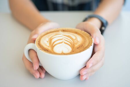 Woman hand holding a white coffee mug.  Coffee is a latte. table on the wooden table in vintage style, taken from the top view, see the froth of milk foam.