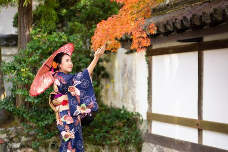 """Geishas girl wearing Japanese kimono among red wooden Tori Gate at Fushimi Inari Shrine in Kyoto, Kimono is a Japanese traditional garment. The word """"kimono"""", which actually means a """"thing to wear"""""""