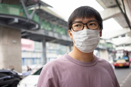 HandsomeMan wearing face mask protect filter against air pollution (PM2.5) or wear N95 mask. protect pollution, anti smog and viruses, Air pollution caused health problem. Global warming concept.