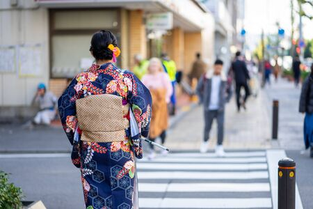 """Geishas girl wearing Japanese kimono among in Kyoto, Kimono is a Japanese traditional garment. The word """"kimono"""", which actually means a """"thing to wear"""""""