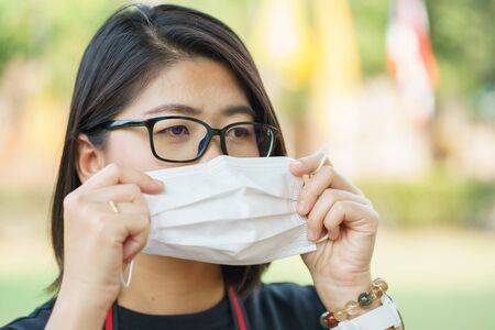 Woman wearing face mask protect filter against air pollution (PM2.5) or wear N95 mask. protect pollution, anti smog and viruses, Air pollution caused health problem. environmental pollution concept.