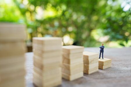 Miniature people  businessmen standing Investment Analysis Or investment. The concept of being the number one business in the world stands at its peak.
