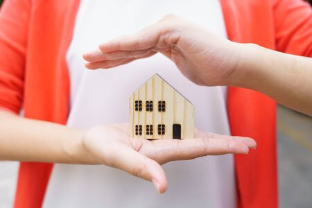 A model house model is placed on The Hands of Asian Business Girl.using as background business concept and real estate concept with copy space for your text or design.