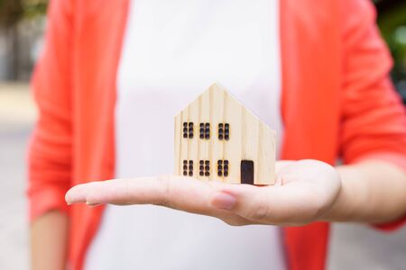 A model house model is placed on The Hands of Asian Business Girl.using as background business concept and real estate concept with copy space for your text or design. Banque d'images - 148517285