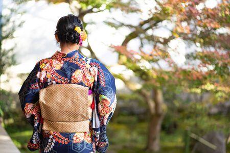 Geishas girl wearing Japanese kimono among red wooden Tori Gate at Fushimi Inari Shrine in Kyoto, Kimono is a Japanese traditional garment. The word