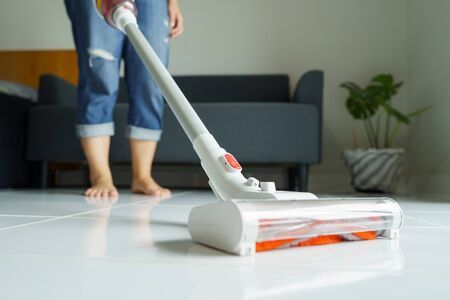 Maid cleaning the house, mop the floor, vacuum using a handheld vacuum cleaner. Eliminate germs and viruses Prevent infection from touching the concept of cleaning the house, housework Banque d'images