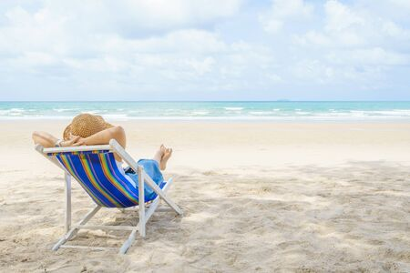 Young Beautiful Asian woman relax in the sun on chairs on the beach near the sea. enjoying looking view of sea with blue sky on summer vacation and travel holiday concept. Banque d'images