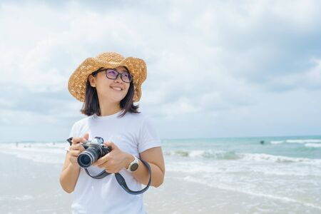 Portrait of Young Beautiful Asian woman relax in the sun on the beach near the sea. enjoying looking view of sea with blue sky on summer vacation and travel holiday concept. Banque d'images