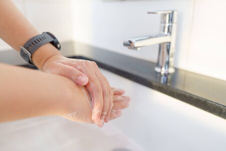 The woman's hand is going to open the faucet to wash hands. To maintain cleanliness after entering the bathroom, the concept of health and cleanliness.
