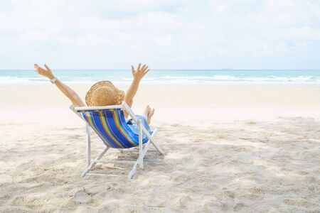 Young Beautiful Asian woman relax with chairs on the beach near the sea. enjoying looking view of sea with blue sky on summer vacation and travel holiday concept. Banque d'images - 148318930