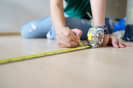 Close up hands woman engineer with yellow carpenters tape measure(measure tape) at construction site. background construction project and ideas concept with copy space.