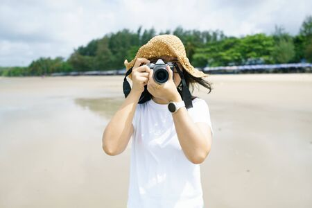 Portrait young woman photography wearing a hat using her mirrorless camera covering her face on the beach and smiling. photography taking concept