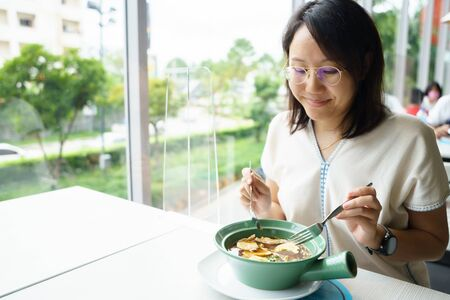 New normal Middle-aged Asian woman Eating food with a plastic plate to prevent the spread of the virus. Social distancing and and keep distance. Stok Fotoğraf
