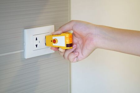 Hand holding electric tester for checking plug at the power outlet in on the wall. Check the quality of electricity in the home. Concept of buying a new home Home inspection And maintenance