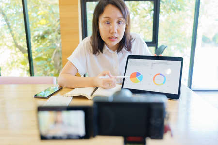 New normal Asian woman aged 30-35 years, vlogger coach presentation training people online. Webcam conference making videoblog and vlogging concept. Banque d'images - 151502132
