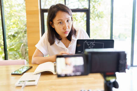 New normal Asian woman aged 30-35 years, vlogger coach presentation training people online. Webcam conference making videoblog and vlogging concept. Banque d'images