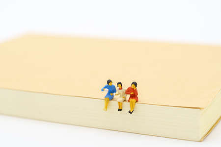 Miniature people sitting on notebook using as background business concept and teamwork concept with copy space and white space.