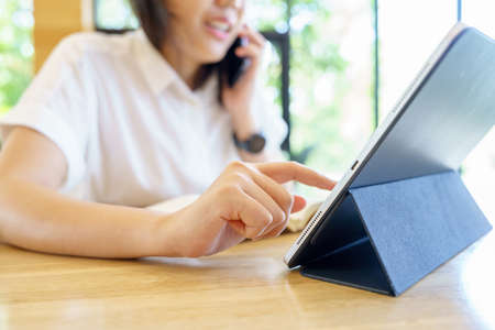 Asian woman aged 30-35 years, using digital tablet technology device enjoying internet study work shopping online using social media apps or playing game on tablet. Banque d'images