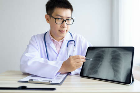 Male asian doctor working in the office hospital. discussing x-ray by using digital tablet. healtcare and assistance concept Stok Fotoğraf
