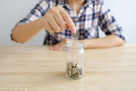 Businesswomen Put the coin in a glass jar To save money, save money on investments, spend money when needed And use in the future. Investment concept. Savings with copy spaces. Stockfoto