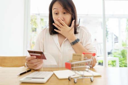 Confused portrait young woman holding credit cards having problem online payment with credit card making rejected unsecure online payment. credit card debt payment Stock fotó - 153218144