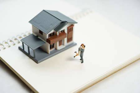 Couple Miniature 2 people standing model with house model make family Feel happy.as background real estate and family concept with copy space. Stock fotó