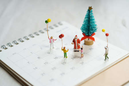 Family Miniature people standing on Christmas tree Celebrate Christmas on December 25 every year. using as background xmas concept with copy spaces for you Stock fotó