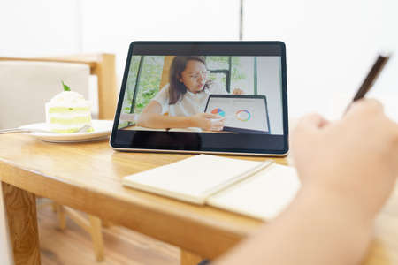 Asian woman aged 30-35 years using tablet, watching lesson online course communicate by conference video call from home, e-learning education concept