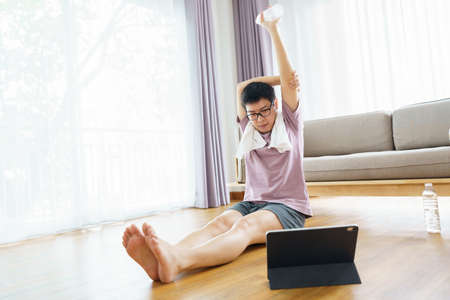 New normal Training At Home An Asian man, aged 35-40, with brown skin, Home exercise. exercising in living room. Stock fotó